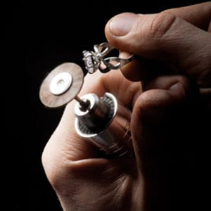 Close up of hands fixing a ring with a grinder
