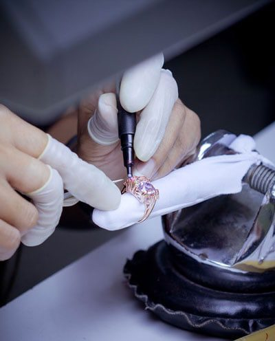 Closeup of jeweler using a hand tool on a ring
