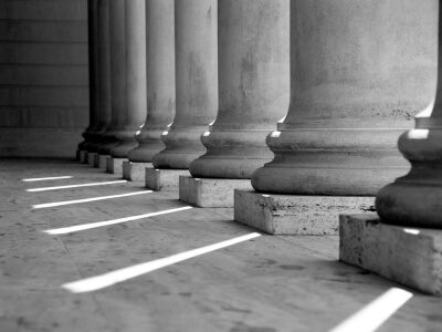 Black and white photo of stone pillars in front of court house