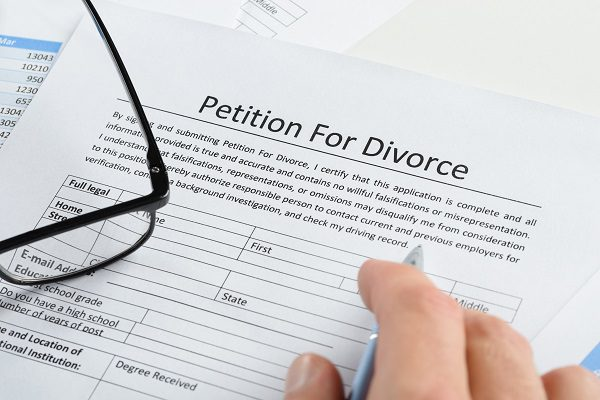 Close-up Of Hand With Pen On Petition For Divorce Paper