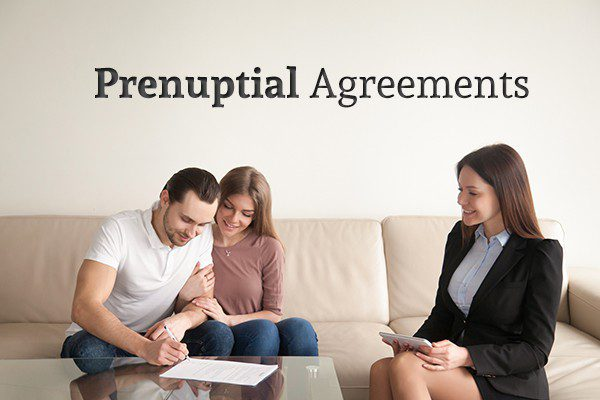 "A happy couple sit on the couch signing a document across from a lawyer under the words ""Prenuptial Agreements"""