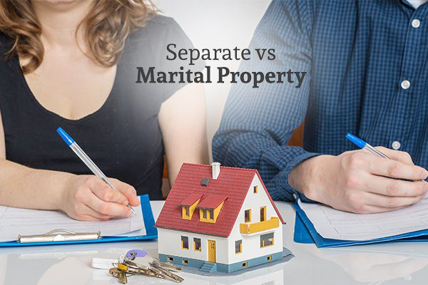 A man and a woman sitting beside each other signing papers with a mini house figure and a set of keys between them and the words separate vs marital property