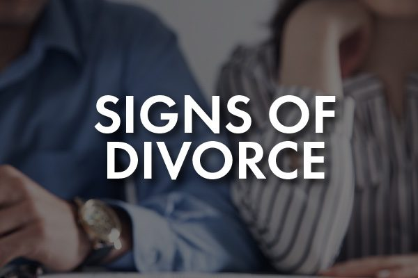 """A couple walking intensely with the words, """"Signs of Divorce"""""""
