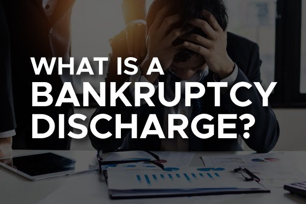 "A person looking over their finances with the words, ""what is a bankruptcy discharge?"""