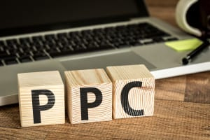 PPC (Pay Per Click) written on a wooden cube in front of a laptop