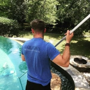 A technician skims debris from a pool during weekly maintenance