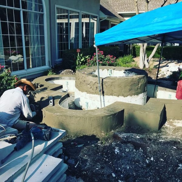 A Liquidus Pro works on remodeling a water feature