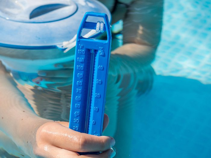 A swimmer checks the temperature of the pool
