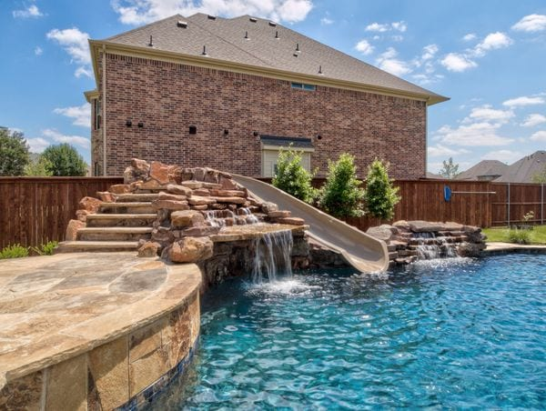 A beautiful pool with a natural looking slide.