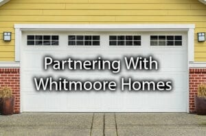 "A beautiful garage door with the words; ""partnering with Whitmoore Homes."""