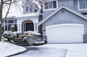 Suburban home with snow on drive way, lawn, plants, trees and roof
