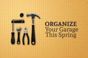 """A hammer, pliers, a wrench, and a screwdriver with a variety of bits hang upon a wall and the words """"Organize Your Garage This Spring"""" are written beside them"""