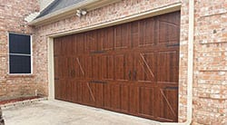 A custom wood residential garage door installed and repaired by technician 2 in Garland Texas by Action Garage Doors of Plano Tx
