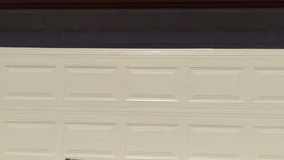 An older residential home in Mckinney Texas having an aged garage door replaced with a new steel door at 6209 Calloway Tx