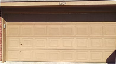 An older residential home that has a very aged garage door needed repairs in Mckinney Texas by Technician 3 Action Garage Doors