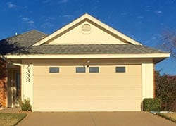 Technician Catherine installed and repaired this windowed steel garage door in a residential home in Garland Texas by Action Garage Doors
