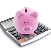A piggy bank standing on a calculator.