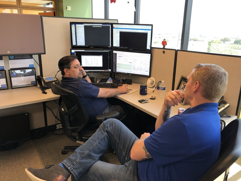two employees talking in a cubicle