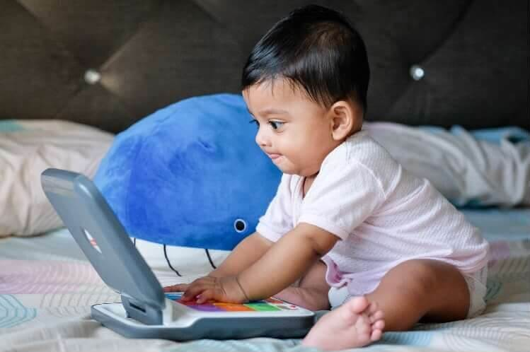 Baby watching computer in bed