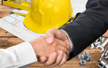 Businessman and contractor shaking hands over a hard hat