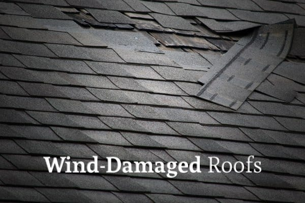 """A roof with some of the shingles blown off with the words """"Wind-Damaged Roofs"""""""