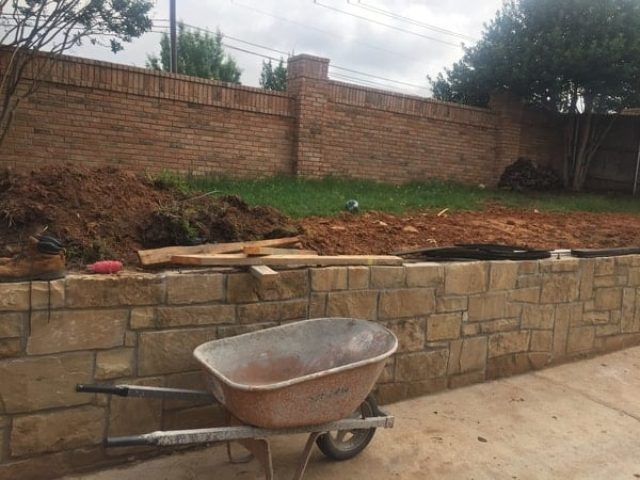 The construction of an immaculate stone retaining wall.