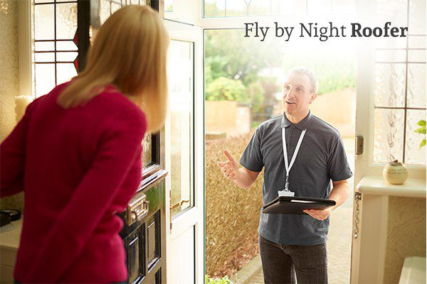 A fly by night roofer pitching his sales call in the entryway of a house while a woman with the door open listens