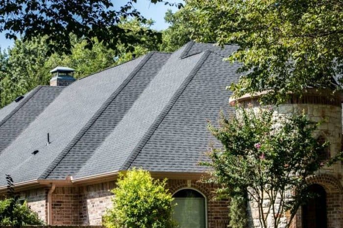 Side angle of a new roof on a beautiful house with nice landscaping.