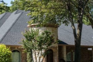 Close-up of a new roof on a beautiful house with nice landscaping.