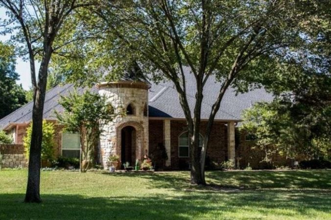 Street view of a ranch-style castle home with a new roof surrounded by nice landscaping.