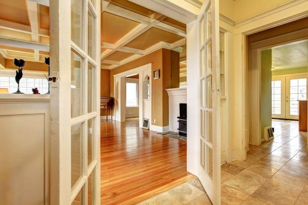 A pair of doors open to show off a beautifully renovated living room.