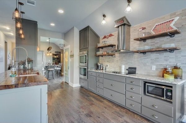 Kitchen remodel with grey cabinets, while tile back-splash, new light fixtures, and hardwood floors