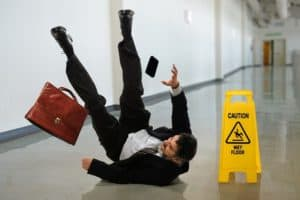 A man slips on a wet floor and falls on his back