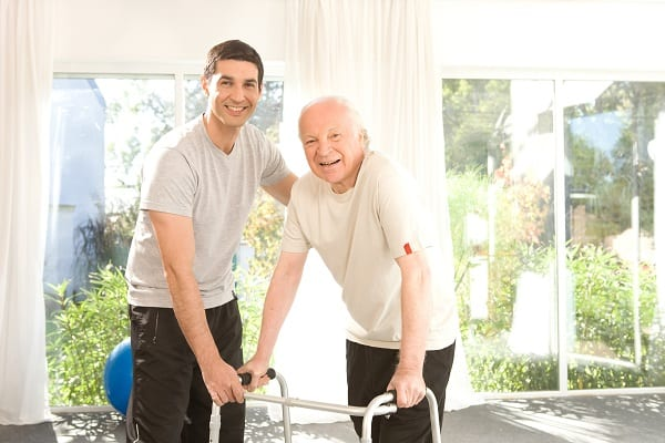 A physical therapist helps an elderly man get around with a walker.