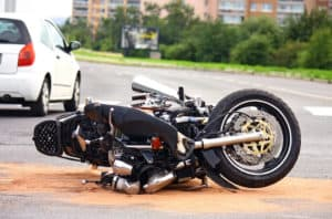A damaged motorcycle lies in the street after an accident