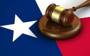 A Legal Gavel rests atop the Texas Flag