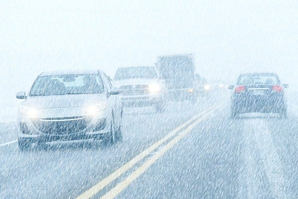 Traffic moves slowly along a busy road during a heavy sleet storm