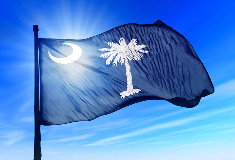 The South Carolina flag is a white crescent and palmetto tree on an indigo field
