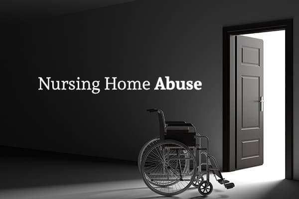 "An empty wheelchair sits in a dark room, highlighted by the sunlight streaming in from the open door in front of it, and the words ""Nursing Home Abuse"" are written over it"