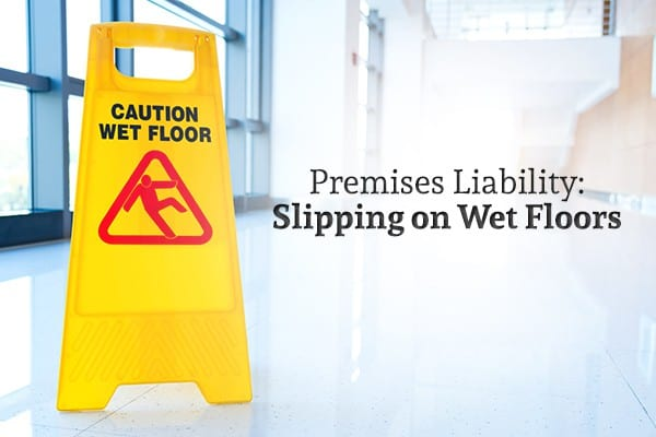 "A wet floor sign sits on a floor beside the words ""Premises Liability: Slipping on Wet Floors"""