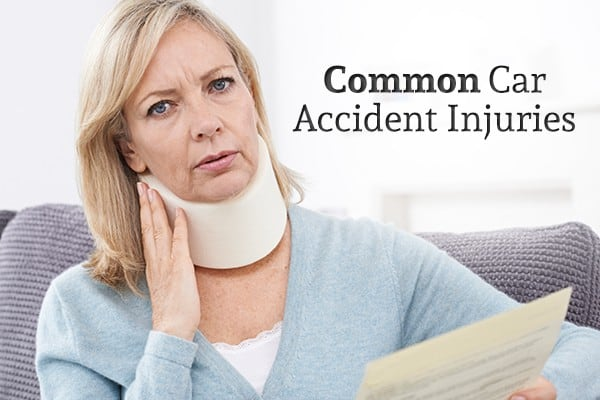 "A woman with a neck brace holds a piece of paper beside the words ""Common Car Accident Injuries"""