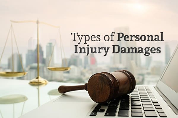 A gavel sits on a laptop in front of a city skyline and words Types of Personal Injury Damages