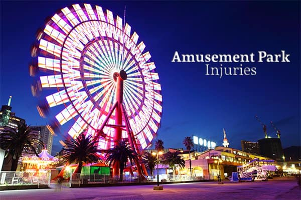"""An amusement park with a Ferris Wheel showing predominantly beside the words """"Amusement Park Injuries"""""""