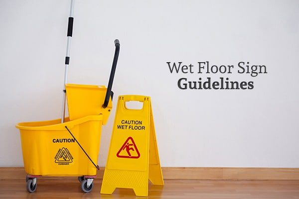 "A mop and bucket beside a wet floor sign on a wood floor, along with the words ""Wet Floor Sign Guidelines"""
