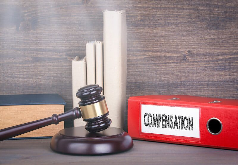 """court gavel beside binder with the words """"compensation"""""""
