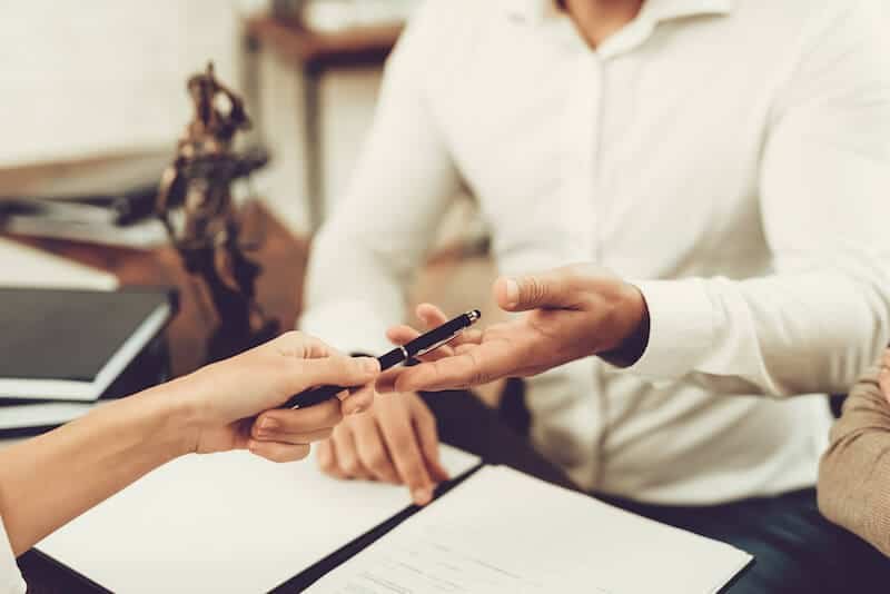 two people exchanging a pen and signing documents