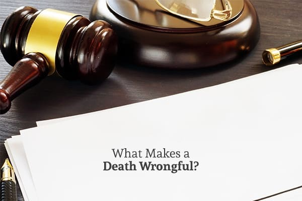 A gavel is sitting near a white piece of legal paper on a desk. Underneath the gavel are the words, what makes a death wrongful.