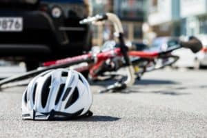 A helmet and a bike on its side are in the middle of the road are in front of a car.