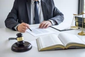 A lawyer going over legal documents with a book, gavel, and a set of legal scales.