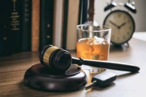 A gavel onto of a desk next to a drink and a clock.